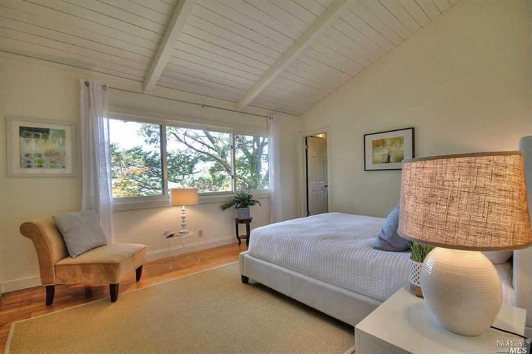 Traditional Guest Bedroom with Hardwood floors, Standard height, six panel door, Exposed beam, picture window