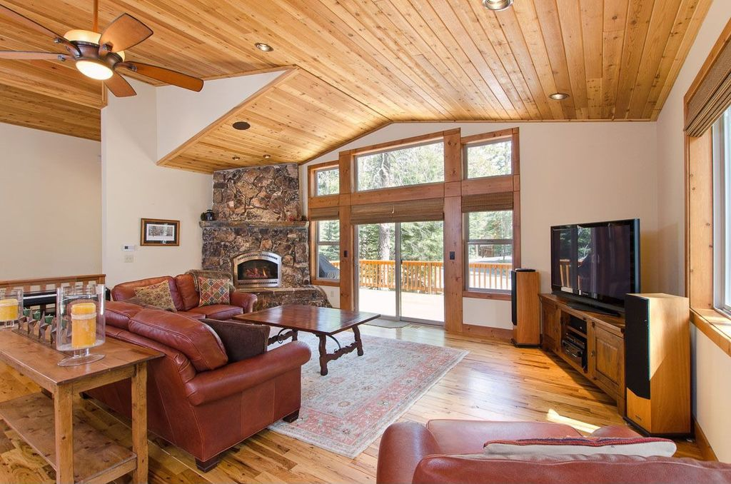 Rustic Living Room with Transom window, Hardwood floors, can lights, Standard height, sliding glass door, stone fireplace