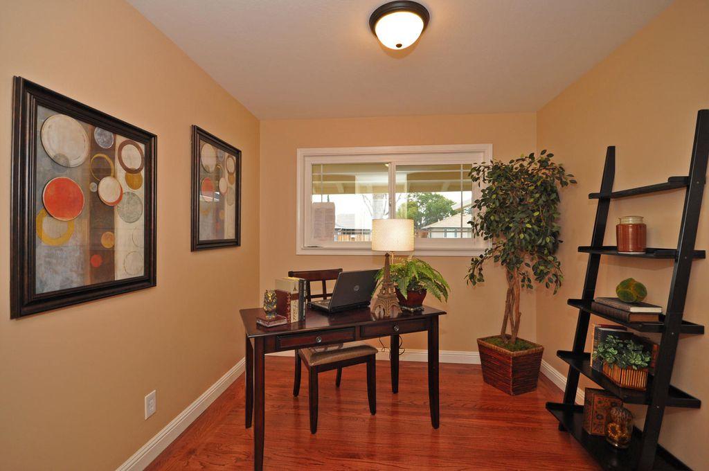 Contemporary Home Office with Casement, flush light, Built-in bookshelf, Hardwood floors, Standard height