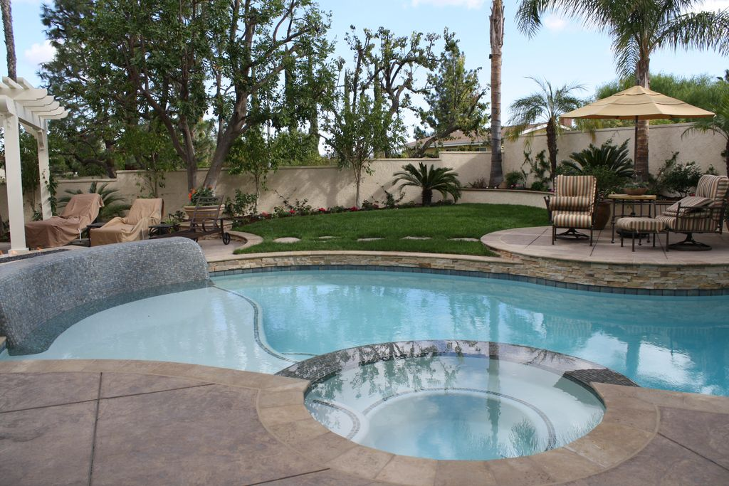 Eclectic Swimming Pool with exterior tile floors, Fence, exterior concrete tile floors, Trellis, Pool with hot tub
