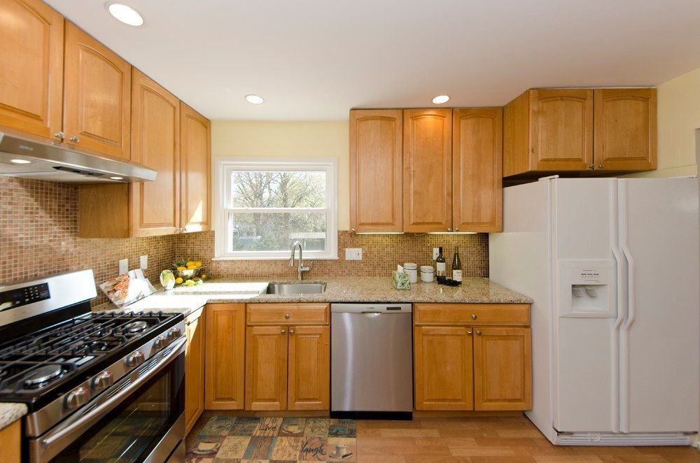 Traditional Kitchen with Raised panel, full backsplash, L-shaped, gas range, can lights, Built In Refrigerator, flush light