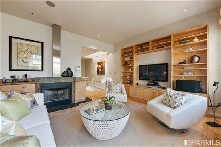 Contemporary Living Room with stone fireplace, Hardwood floors, Built-in bookshelf, Fireplace, Standard height, can lights