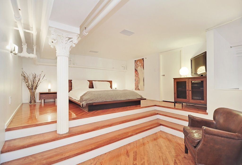 Contemporary Master Bedroom with Hardwood floors, High ceiling, Columns, Wall sconce, Exposed beam, flat door