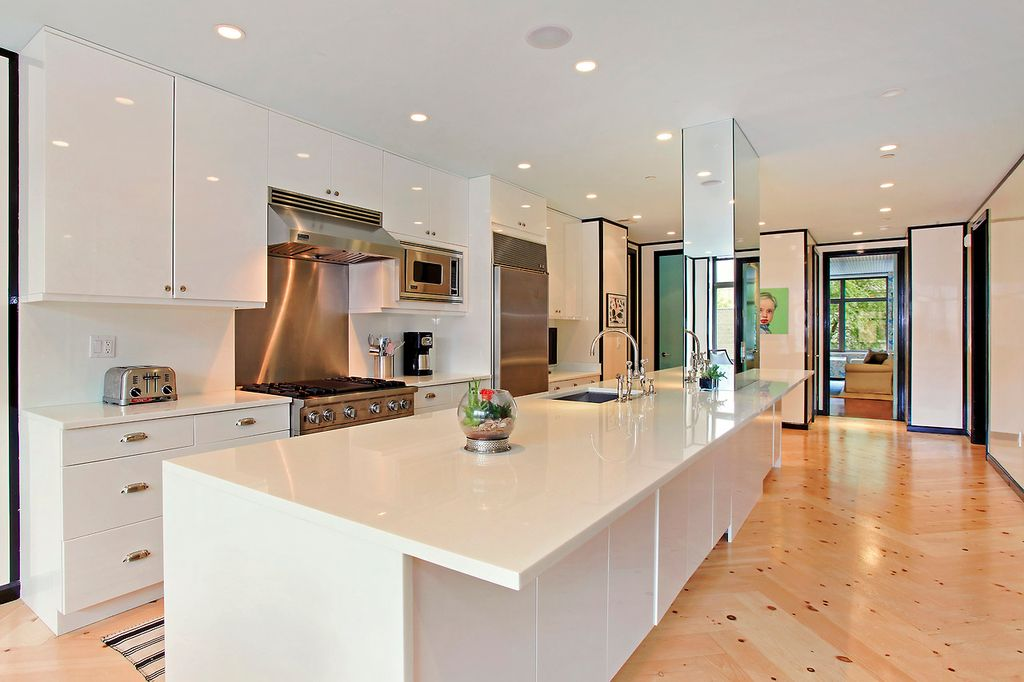 Contemporary Kitchen with gas range, Stainless Steel, Flush, can lights, Corian counters, Built In Refrigerator, Wall Hood