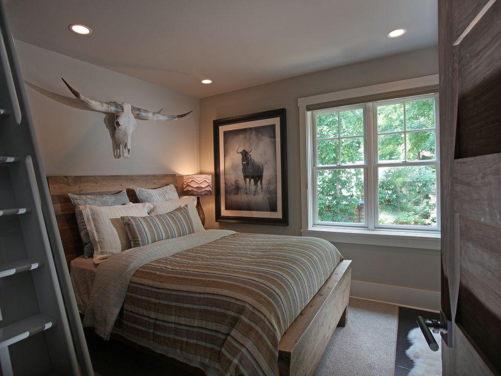 Rustic Guest Bedroom with stone tile floors, can lights, specialty door, soapstone tile floors, Built-in bookshelf