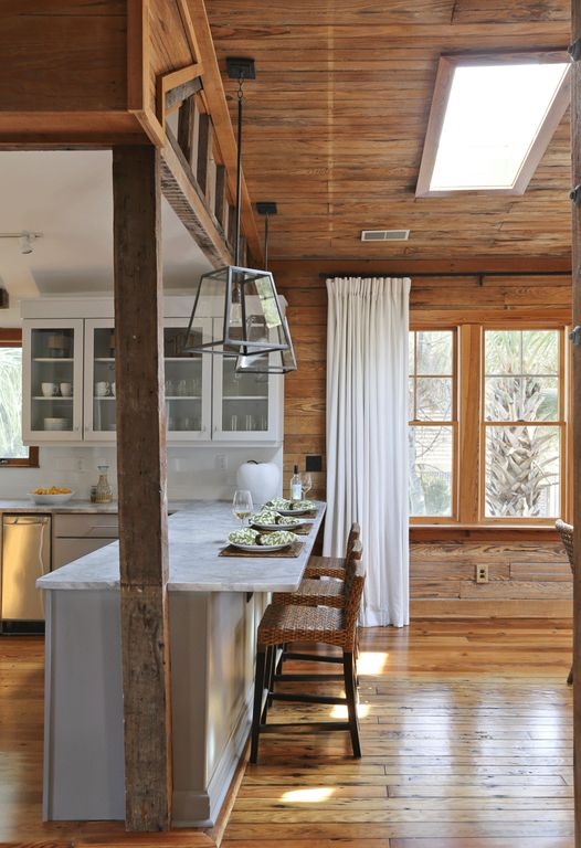 Cottage Dining Room with Marble countertop, Hardwood floors, Exposed wood ceiling, Industrial trapezoid pendant light