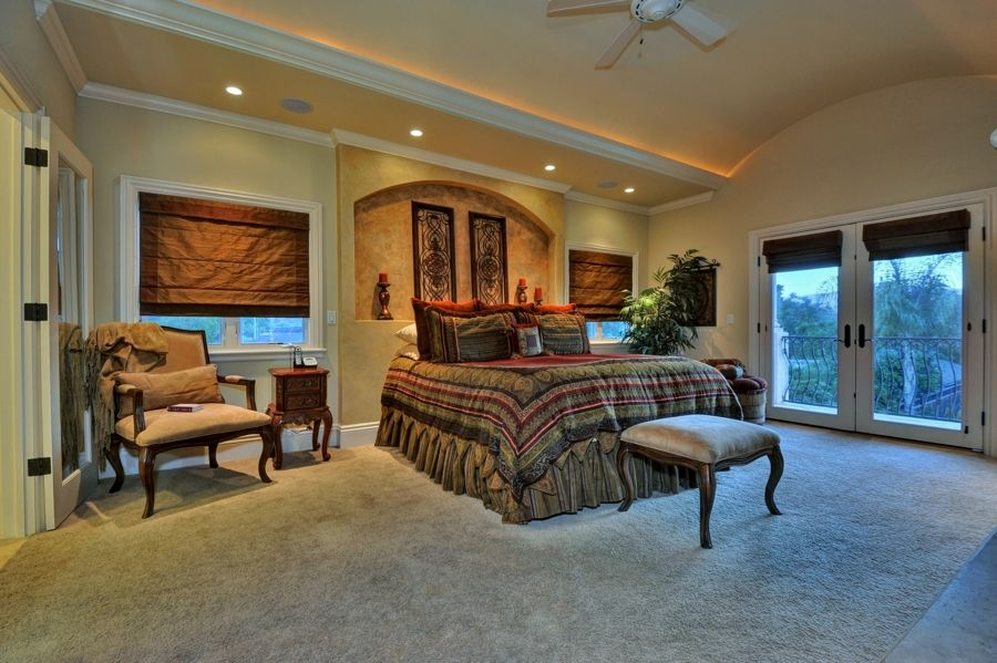 Mediterranean Master Bedroom with Crown molding, High ceiling, Ceiling fan, Casement, French doors, Concrete floors