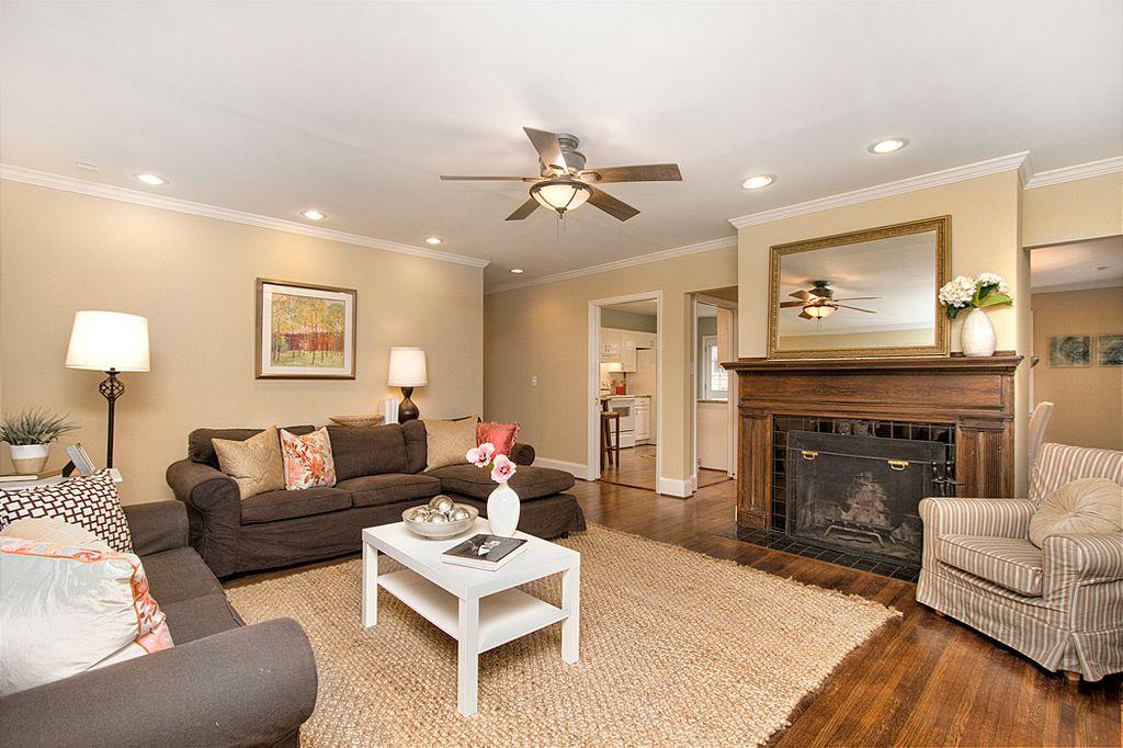 Craftsman Living Room with can lights, brick fireplace, Hardwood floors, Standard height, Ceiling fan, Fireplace, flush light