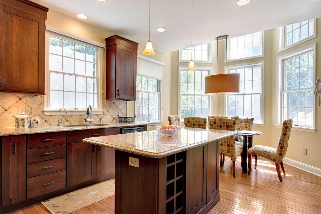 Traditional Kitchen with Flat panel cabinets, Pendant light, full backsplash, Kitchen island, dishwasher, Stone Tile, Flush