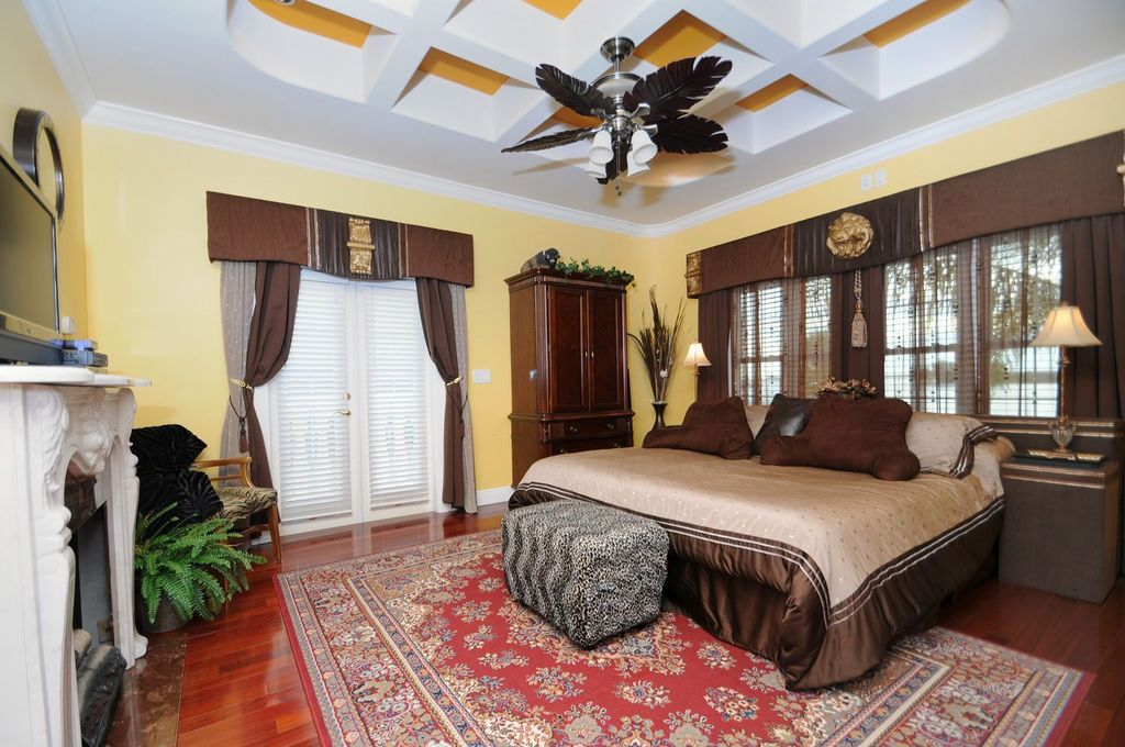 Traditional Guest Bedroom with Fireplace, Louvered door, Box ceiling, flush light, double-hung window, Hardwood floors