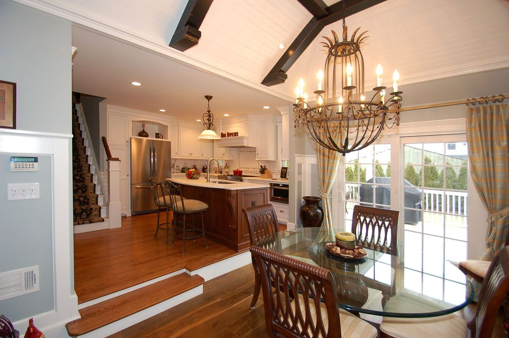 Traditional Dining Room with Exposed beam, Wainscotting, Hardwood floors, Crown molding, Chandelier