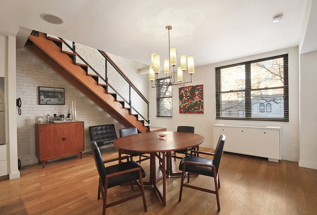 Contemporary Dining Room with Standard height, Hardwood floors, interior brick, double-hung window, Chandelier