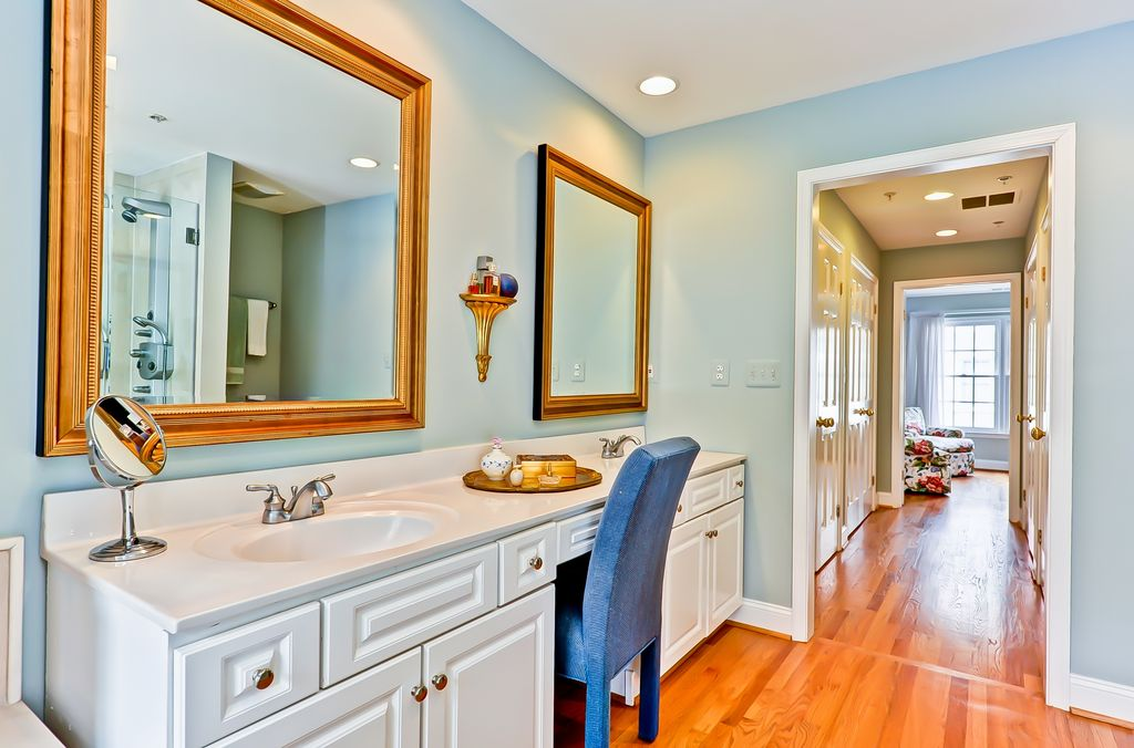 Traditional Master Bathroom with Hardwood floors, Standard height, Raised panel, Shower, Double sink, Corian counters