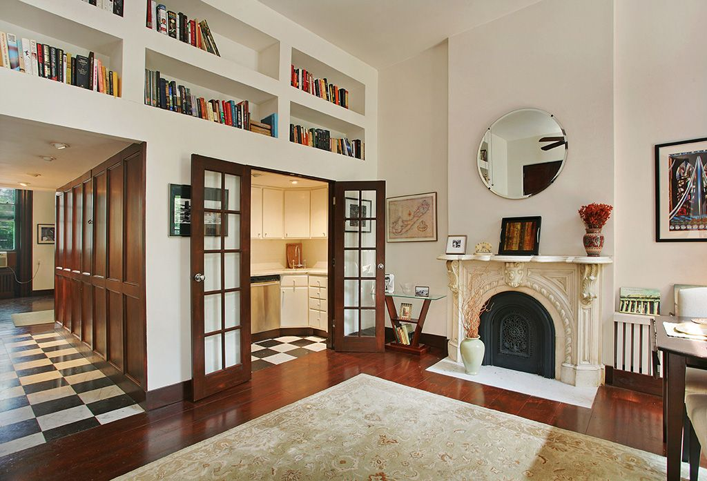 Eclectic Living Room with Built-in bookshelf, Fireplace, Hardwood floors, High ceiling, French doors, Cement fireplace