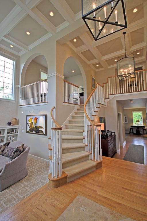 Traditional Staircase with Box ceiling, Chandelier, curved staircase, can lights, Hardwood floors, Standard height
