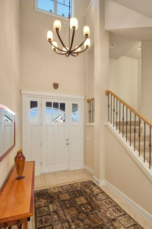 Traditional Entryway with Glass panel door, Chandelier, picture window, High ceiling, Columns, stone tile floors