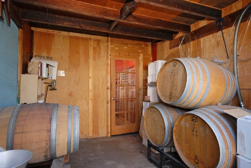Rustic Wine Cellar with Concrete floors, French doors, Exposed beam, Standard height
