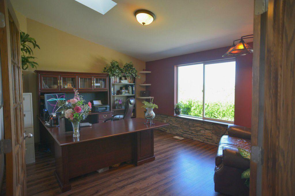 Rustic Home Office with Casement, flush light, French doors, Hardwood floors, Standard height, Built-in bookshelf