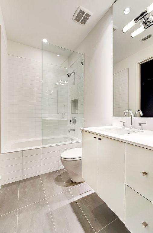 Modern Full Bathroom with Flush, Full Bath, full backsplash, drop in bathtub, stone tile floors, can lights, Corian counters