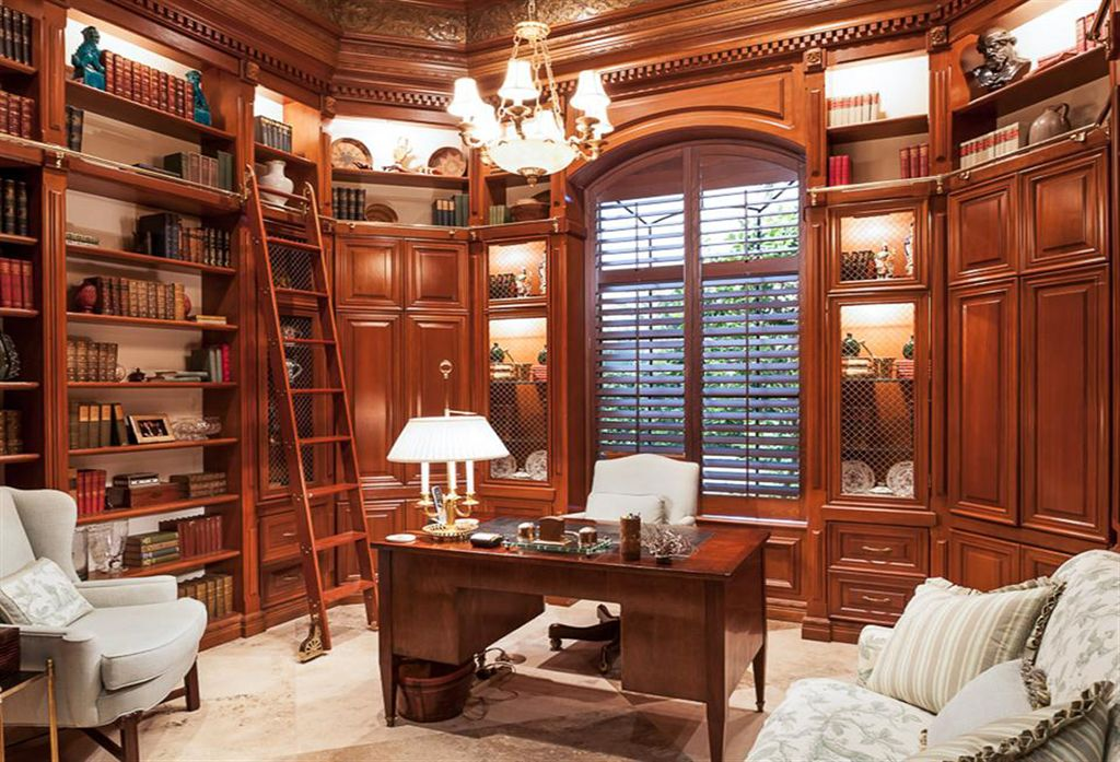 Traditional Home Office with Built-in bookshelf, travertine floors, Arched window, Crown molding, Chandelier