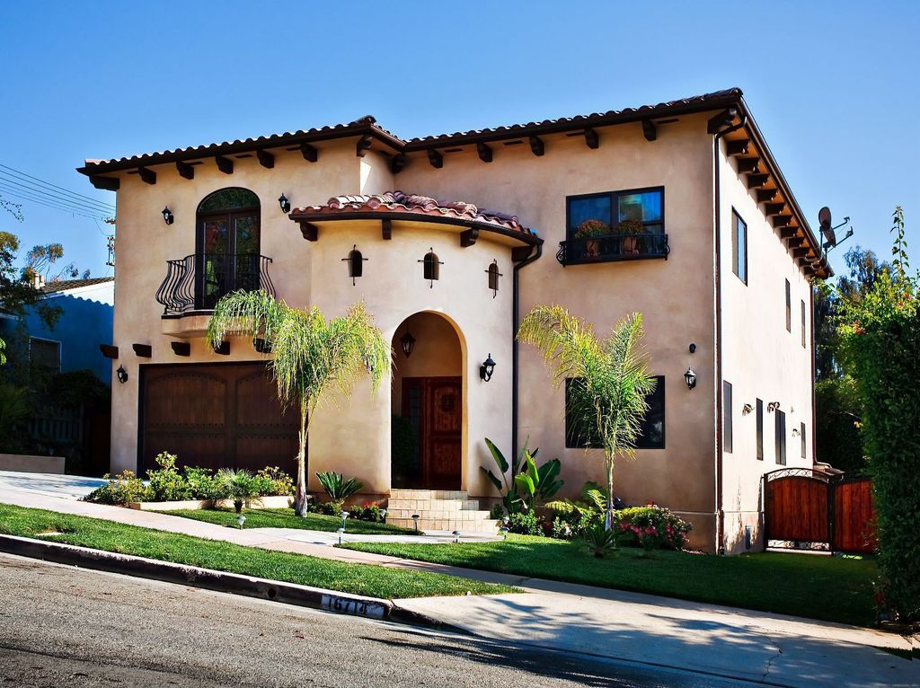Mediterranean Front of Home with Deck Railing, six panel door, Gate, exterior concrete tile floors, Casement, Arched window