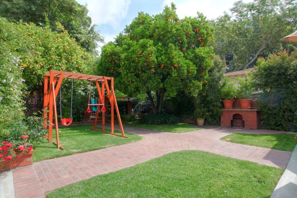 Mediterranean Landscape/Yard with Fence, Pathway, outdoor pizza oven, Raised beds, Gate, exterior brick floors