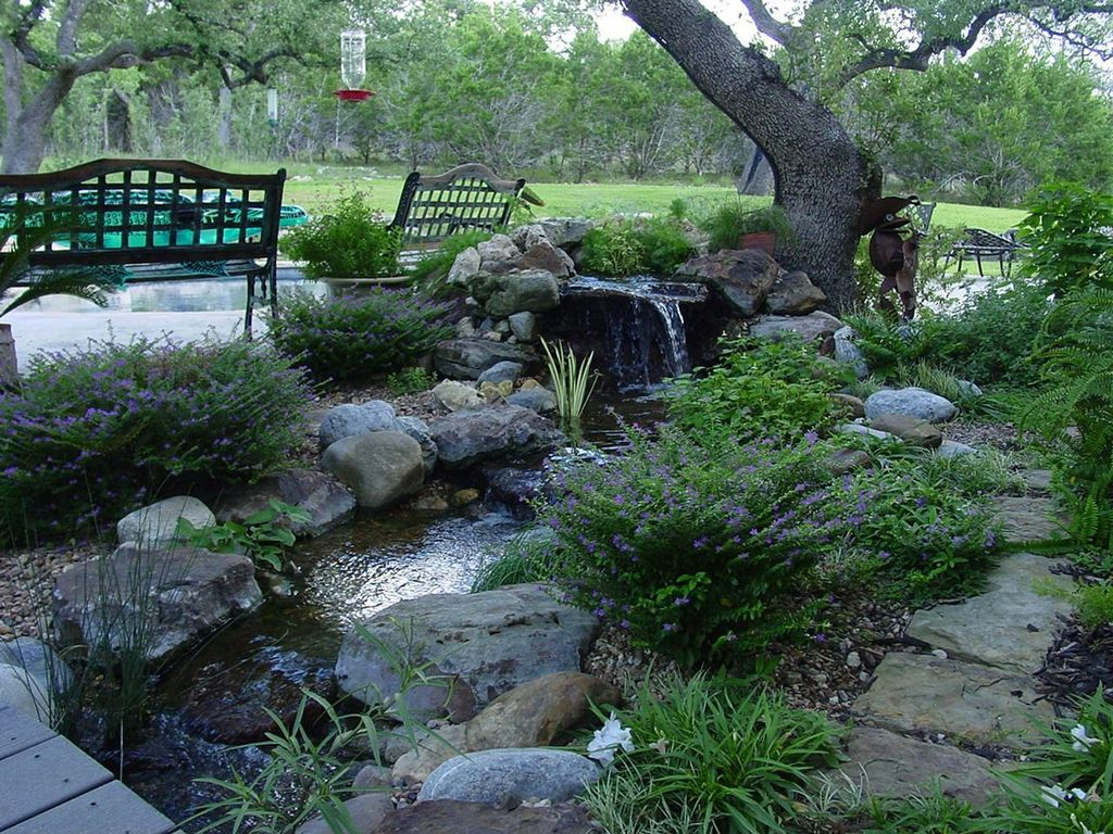 Traditional Landscape/Yard with Pond, exterior concrete tile floors, Pathway, Water feature, Naturalistic landscaping